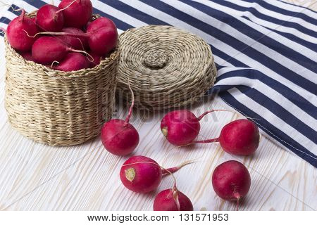 Red radishes in a basket on wooden desk