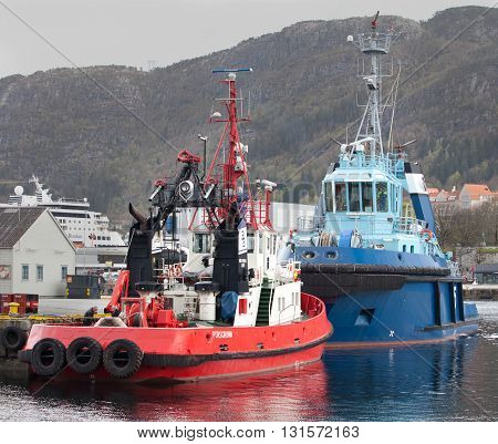 BERGEN, NORWAY - MAY 15, 2012: Two tugboats - red Bever and blue Silex at pier in Bergen