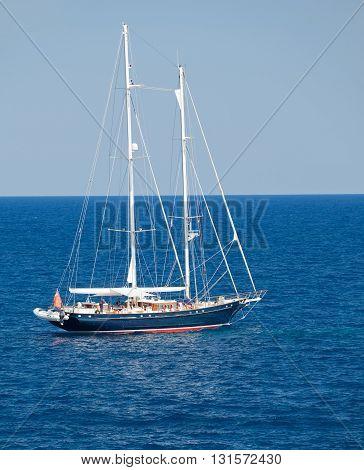 MALLORCA, SPAIN - JULY 25, 2012: Dark blue yacht in the coastal waters of Mallorca