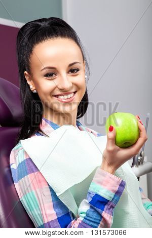 Beautiful Woman Patient In Dental Chair Smiling With Green Apple
