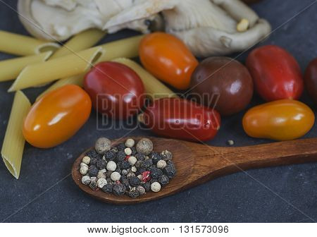 food products - mushrooms plate  with tomatoes and mix different peppers peas on the spoon