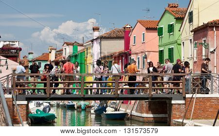 VENICE, ITALY - JUNE 28, 2013: Tourists on a bridge of the Burano island