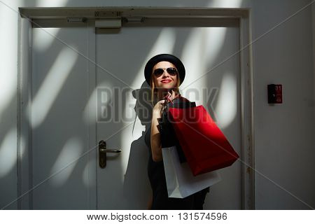 Stylish woman leaving a shop with paper bags
