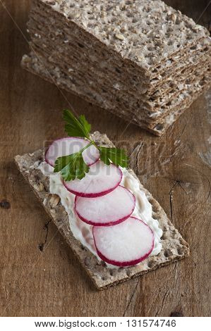 Radishes on crispbread on a wooden background