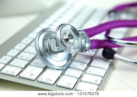 Silver stethoscope lying on a keyboard, isolated.
