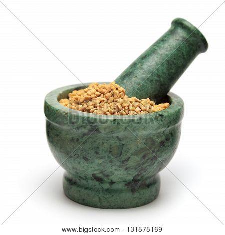 Organic Fenugreek (Trigonella foenum-graecum) on marble pestle. Isolated on white background.