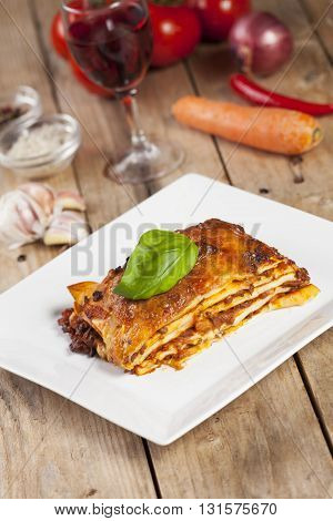 lasagna portion on a white plate with wine