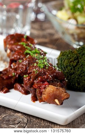 shashlik skewers with broccoli on a white plate