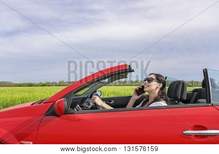 Woman drives the car on the country road and talking on the phone in good humor.