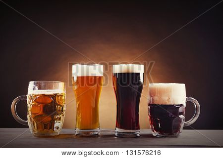 Different sorts of draft beer in glasses on wooden table. Retro stylization