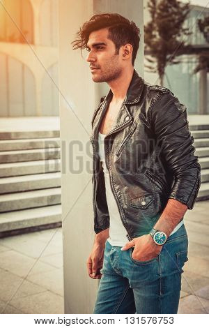 Stylish man in the white T-shirt, leather jacket and jeans standing near a column in a modern architectural environment