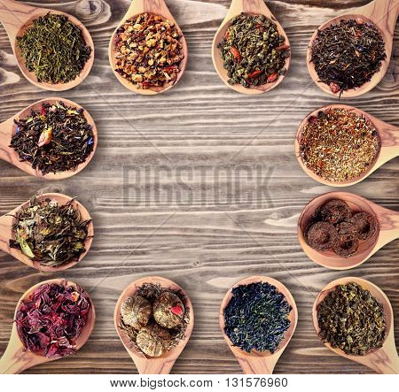 Set of different tea in wooden spoons on wooden background