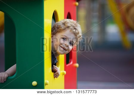 Small curly boy is hiding in the playground