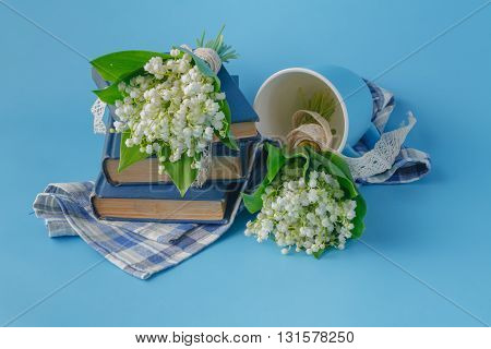 Lilies Of The Valley And Books On Blue Background