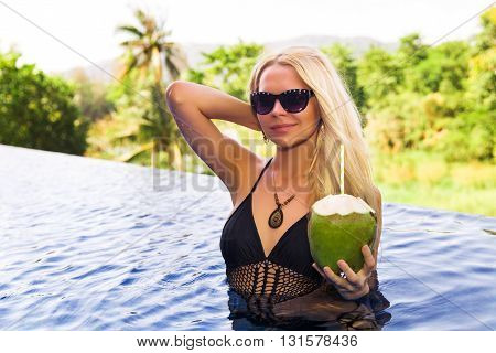 Young Pretty Blonde Woman In Swimming Pool With Coconut Coctail