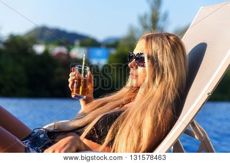 Young Slim Woman With Glass Of Juice Near Swimming Pool