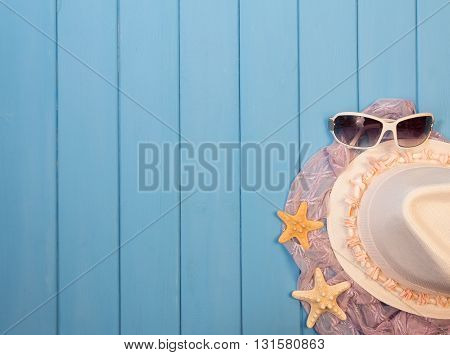 Beach accessories: hat, sunglasses, pareos and starfish on a background of blue painted wood.