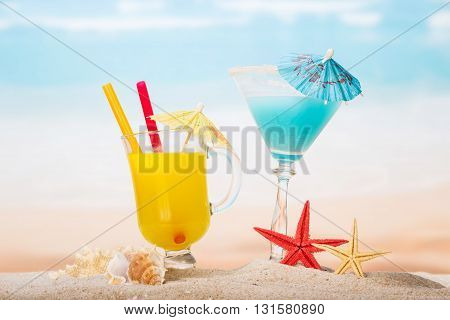 Cocktail, orange juice, starfish and shells on the beach.