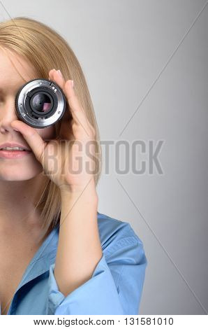 Young Woman Using Camera Lens Over Gray Background