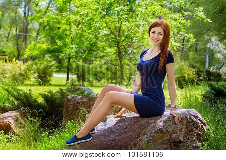 Beautiful young smiling woman with long red hair wearing short casual blue dress and moccasins sitting on the rock in the park