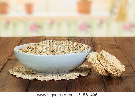 A bowl of oatmeal and crispbread on a background of dark wood.