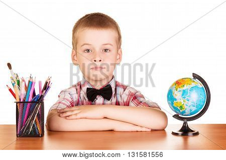Cute schoolboy, globe and pencils on the table isolated on white background.