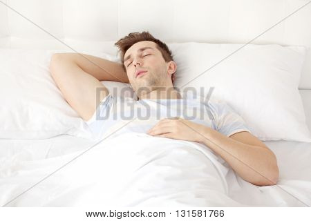Young man sleeping on comfortable bed