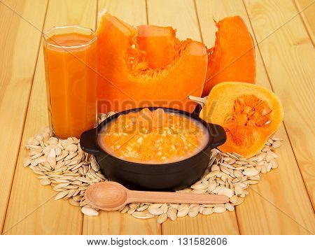 Slices of pumpkin, a glass of juice, cereal, seeds and a wooden spoon on a background of light wood.