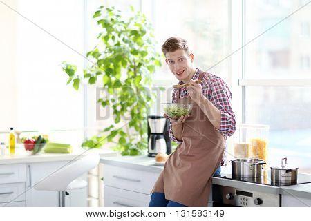 Happy handsome man eating vegetable salad in bright kitchen