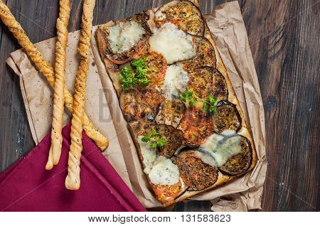 Traditional Focaccia with eggplant and tomatoes on wood