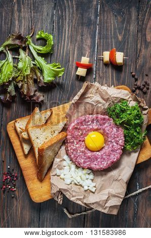 Beef tartare with bread and fresh onion on a wooden background.