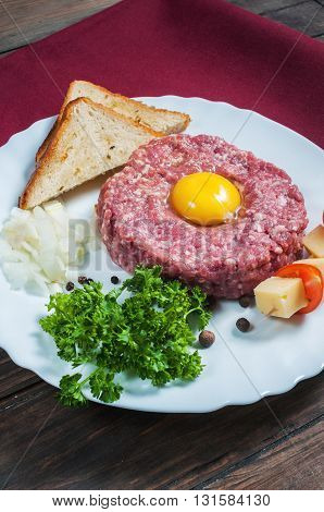 Beef tartare with bread and fresh onion on a wooden background