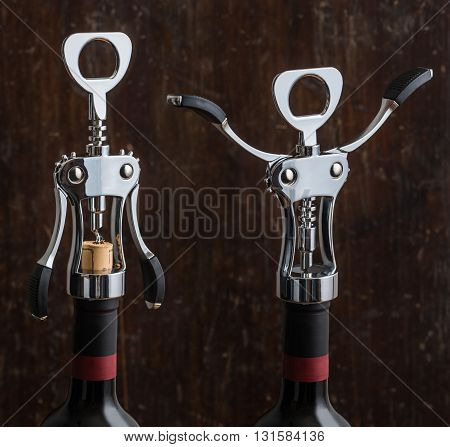 Glossy Metal Wing Corkscrew Opening a Bottle of Wine on Wooden Background. Wine Bottle Opener with Wings Closed and Opened.