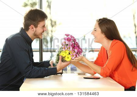 Profile of a couple dating and looking each other with a man giving a bouquet of flowers to his partner in a coffee shop