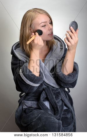 Portrait Of Attractive Woman In Bathrobe Doing Her Makeup