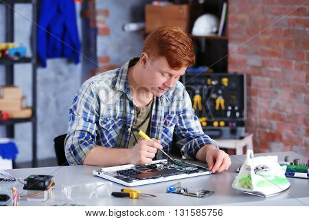 Young man working in repair center