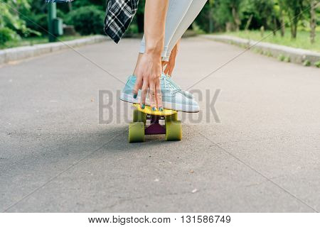 Girl Rides On A Skateboard On Asphalt And Holds Balance