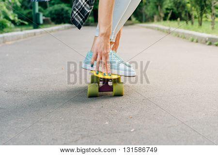 Girl Rides On A Skateboard On Asphalt And Holds Balance