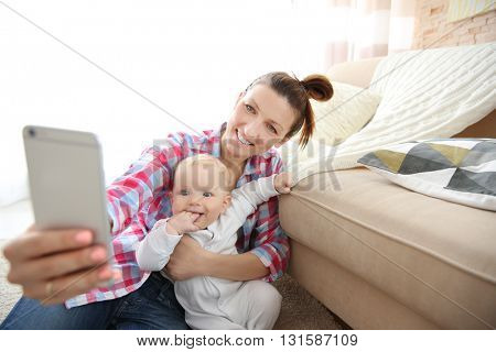 Young mother taking a selfie with her baby near the couch, close up