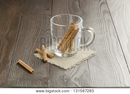 Glass cup with cinnamon sticks on a linen napkin . Focus is on the cinnamon sticks