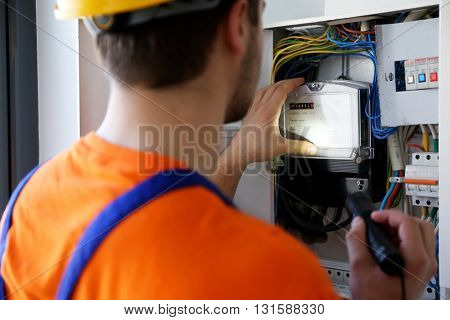 Man with flashlight checking switch box closeup
