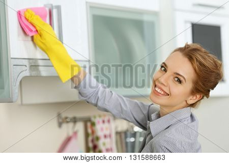 Young woman scrubbing the kitchen cupboard with a rag