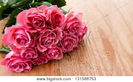 Pink rose  bouquet over wooden table. Wooden background.Top view with copy space