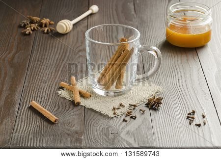 Glass cup with cinnamon sticks on a linen napkin with honey . Focus is on the cinnamon sticks