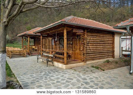 Lisine Serbia - April 03 2016: Porch on the houses made of logs of wood with garden furniture of bamboo