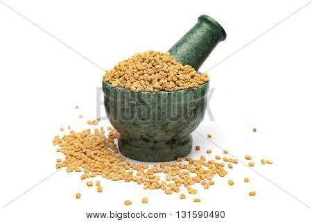 Organic Fenugreek (Trigonella foenum-graecum) on marble pestle and white background.