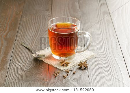 Glass cup of tea with spice on a wooden background