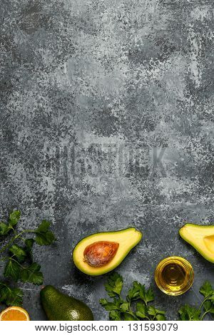 Food background with avocado lemon parsley and olive oil on concrete surface top view copy space.
