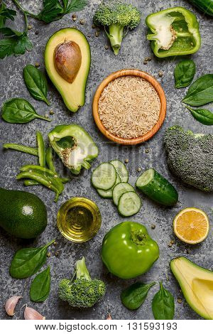 Composition vegetarian diet foods - green vegetables rice and olive oil top view. Vegan diet healthy eating concept.