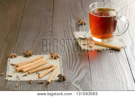 Glass cup of tea on a linen napkin with cinnamon sticks and spice. Focus is on the cinnamon sticks.